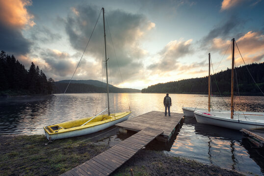 Rear view of a man with backpack, enjoying the sunrise at a wooden pier of a picturesque mountain lake beach