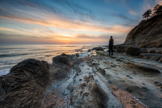 Rear view of a man enjoying the sunrise at a picturesque rocky beach