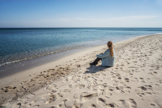 Young woman in jacket sitting on lonely autumn beach and looking into distance