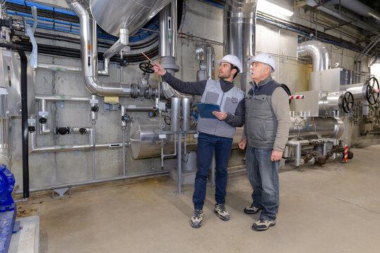 men looking at steel equipment in factory