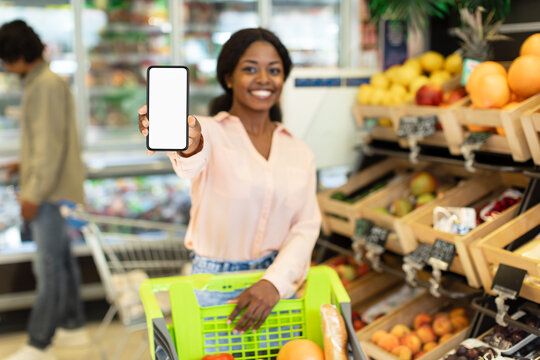 Black Woman Advertising Grocery Shopping Application Showing Phone In Supermarket