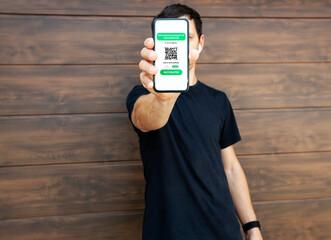 Obraz The man showing digital health passport app in mobile phone for travel. - fototapety do salonu