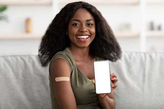 Attractive vaccinated afro-american woman showing smartphone, mockup, home interior