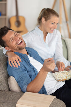 young couple laughing while watching tv at home