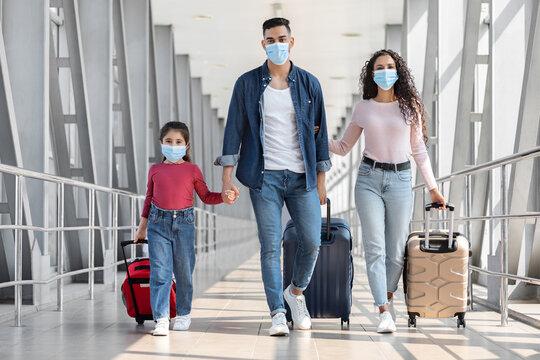 Pandemic Travels. Arab Family Of Three Wearing Protective Masks Walking At Airport