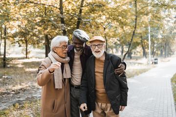 Fototapeta Senior african american man hugging interracial friends in eyeglasses in autumn park obraz