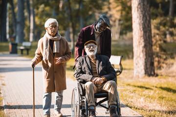 Fototapeta Cheerful man in wheelchair near interracial friends in autumn park obraz