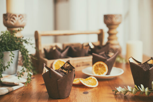 Chocolate and orange Muffins on a wooden table