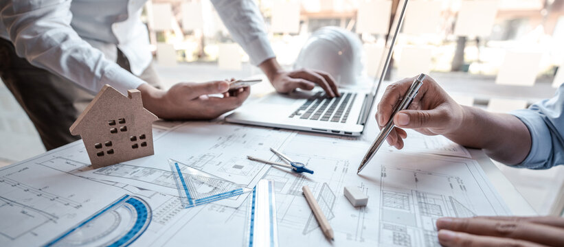 Architects or engineering team consulting and analyzing working on objects tools and construction drawings inspection planning new architectural project on blueprint and model house in modern office