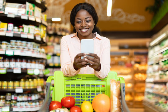 African American Lady Posing With Cellphone And Cart In Supermarket