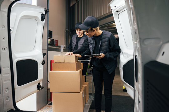Male courier pushing a cart in a warehouse while coworker checking the number of boxes