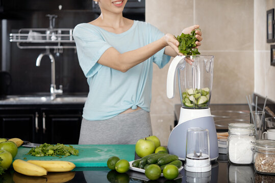 Smiling woman leading healthy lifestyle adding ingredients into blender while mixing green smoothie