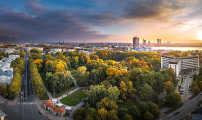 Park in Riga with trees in autumn colors. Colorful sunset over the city panorama. Downtown in...