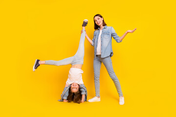 Fototapeta Photo of pretty charming siblings dressed denim shirts fooling standing arms smiling isolated yellow color background obraz