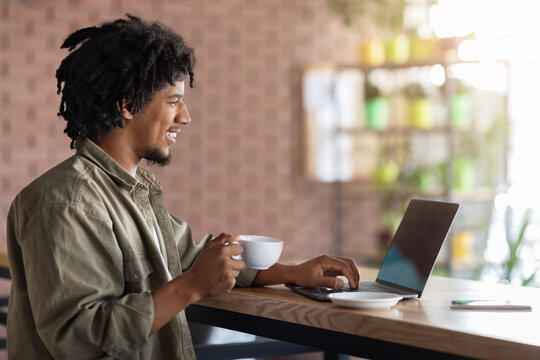 Young Black Freelancer Guy Working With Laptop And Drinking Coffee At Cafe
