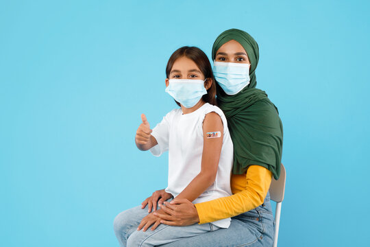 Vaccinated Islamic Mother And Daughter Gesturing Thumbs-Up Over Blue Background