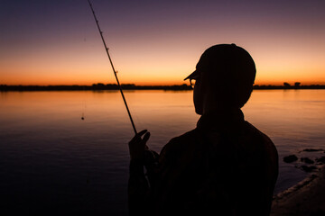 Silhouette of a man fishing relaxed on the edge of the river with the sunset in the background.