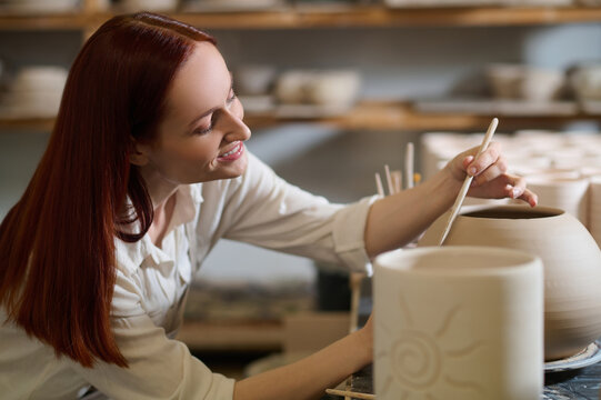 A cute female potter looking involved while painting the pot