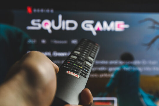 Watching Squid game show on TV. Squid game is a South Korean survival drama television series streaming on Netflix