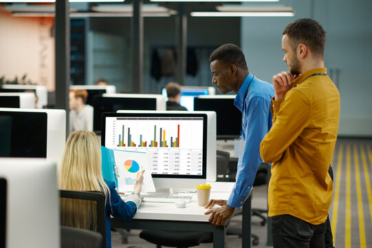 Team of managers looks on charts in IT office