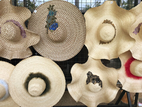 Various styles of woven hats are hung for sale and show customers to buy.