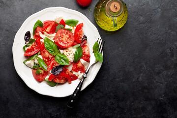 Obraz Caprese salad with fresh tomatoes, garden basil and mozzarella cheese - fototapety do salonu