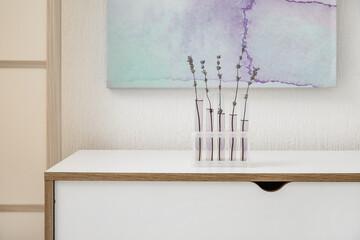 Fototapeta Flasks with beautiful lavender flowers on table in room obraz