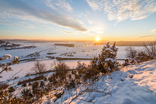 Scenic sunset over snowy winter landscape in the Swabian Alps with bushes and trees in the foreground