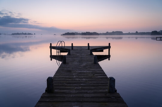An empty jetty in a lake during a tranquil, foggy dawn.