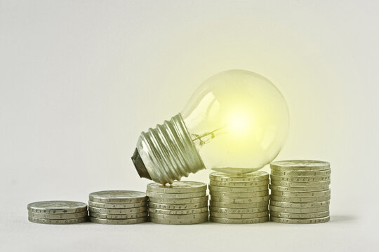 Electric light bulb on raising piles of coins -  Concept of increase in electricity bills