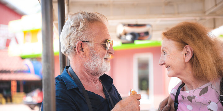 Portrait of loving and caring senior husband and wife on a vacation with a camera round the neck eating ice-cream while smiling and looking at camera