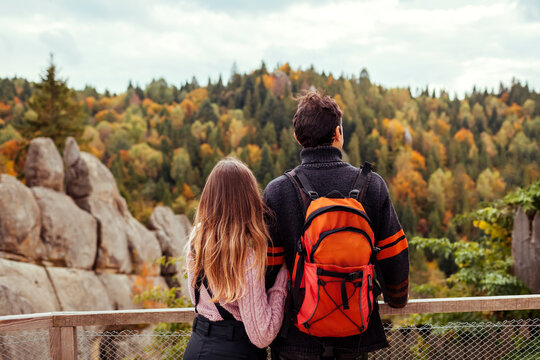 Couple of travelers with backpack admire landscape by rocks in Tustan in autumn Carpathian mountains. Tourism in Ukraine