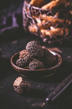 Black truffle in bowl on dark background
