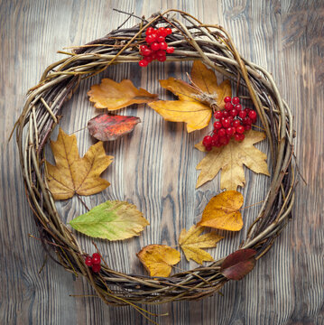 Wreath of twigs on an old wooden door with autumn berries and a leaf