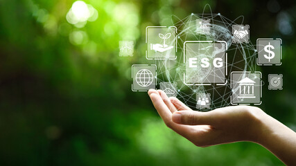 Obraz ESG icon concept in the hand for environmental, social, and governance in sustainable and ethical business on the Network connection on a green background. - fototapety do salonu