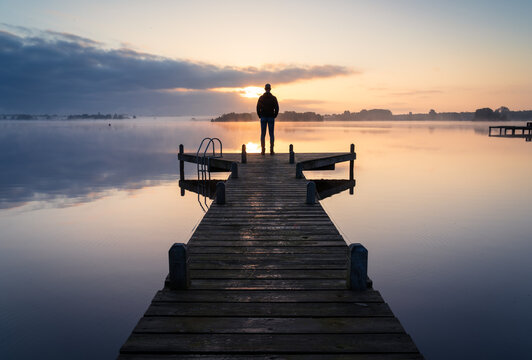 A man looking over a lake during a foggy, tranquil morning.