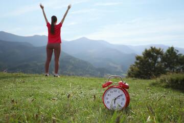 Fototapeta Woman doing morning exercise in mountains, focus on alarm clock obraz