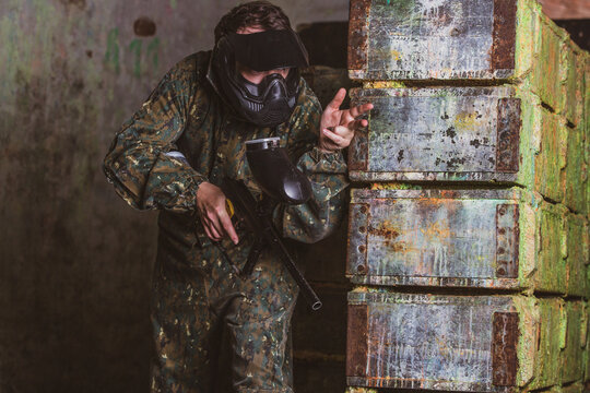 Young man in a paintball action with professional equipment, mask, gun and protective helmet, simulate military combat using air guns to shoot capsules of paint at each other