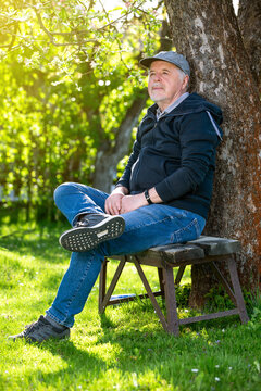 Portrait of a senior man outdoors, sitting on a bench in a park, optimism, good health, expression, retirement or pension concept