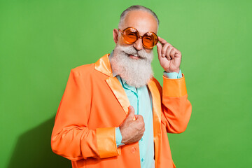 Obraz Portrait of attractive cheerful grey-haired man touching orange specs posing isolated over bright green color background - fototapety do salonu
