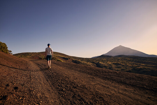 Rear view of man walking on dirt road against beautiful volcanic landscape at sunset. Volcano Teide, Tenerife, Canary Islands, Spain..