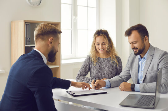 Young married couple decide to buy or rent house. Happy husband and wife sitting at office table and signing contract agreement given by professional realtor or real estate agent
