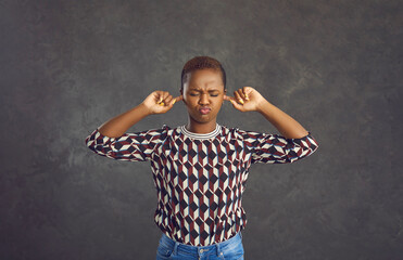 Obraz Capricious young African American woman covers her ears with her fingers so as not to hear anything. Woman with short hair dressed in jeans and a sweater stands with a frown on a gray background. - fototapety do salonu