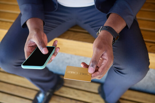 Close up picture of a man holding a credit card and a smartphone