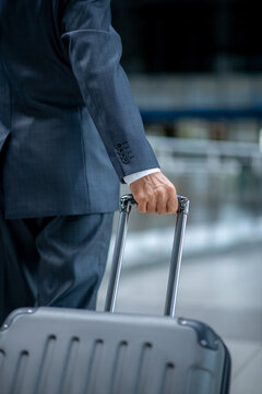 Male hand carrying suitcase at airport