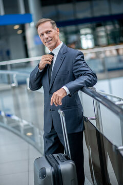 Man in suit straightening tie in airport lounge