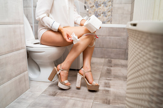 Elagant young woman sitting on toilet and holding toilet paper