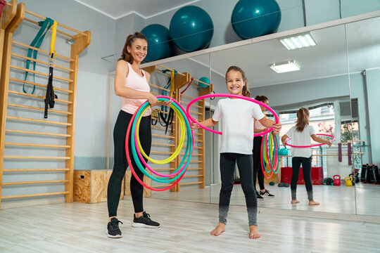 Little girl with hoola hoop in the gym with her pe teacher or trainer, kids health and activity