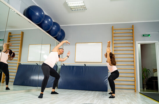 Two woman in gym doing ballet stretches