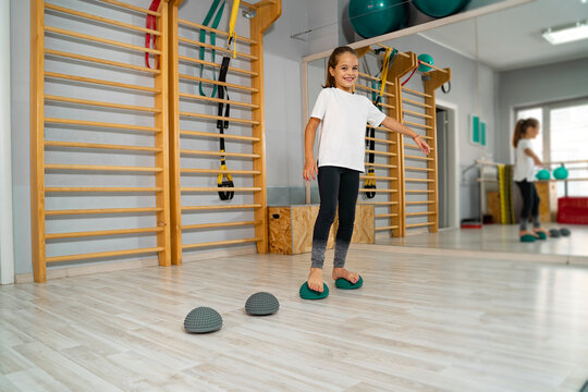 Little girl stepping on rubber balls for flat feet correction